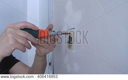 Unscrewing The Bolts In The Body Of The Old Electrical Switch With A Screwdriver During The Replacem