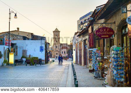 Larnaca, Cyprus - Feb 18, 2019: Couple Walking By A Street Full Of Tourist Shops To The Saint Lazaru
