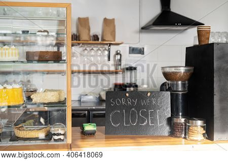 Closed Sign Board On The Bar Counter In An Empty Coffee Shop. Cafe, Bar Closed Due Outbreak Lockdown