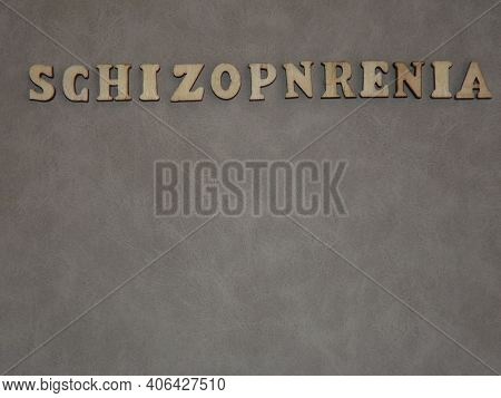 Mental Illness-schizophrenia In The Form Of Wooden Letters And Figures Of People On A Gray Backgroun