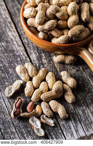 Roasted peanuts. Tasty groundnuts on wooden table.