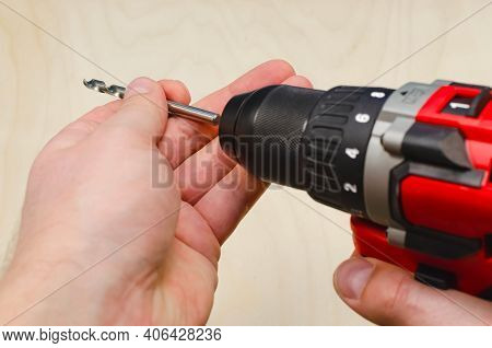 Installs The Drill Into The Drill, Hands Take The Drill And Install It Into The Electric Drill