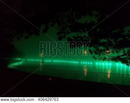 Mystery Mist Over Pond With Bright Green Illumination And Blurry Reflection In Calm Water. Night Lan