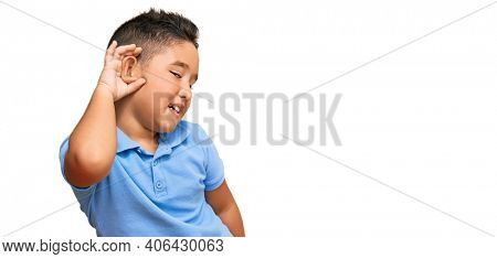 Little boy hispanic kid wearing casual clothes smiling with hand over ear listening an hearing to rumor or gossip. deafness concept.