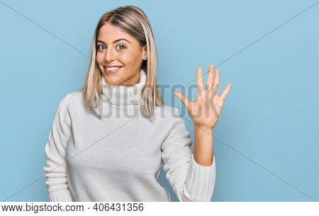 Beautiful blonde woman wearing casual turtleneck sweater showing and pointing up with fingers number five while smiling confident and happy.