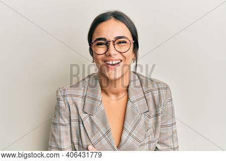 Young brunette woman wearing business jacket and glasses smiling and laughing hard out loud because funny crazy joke with hands on body.