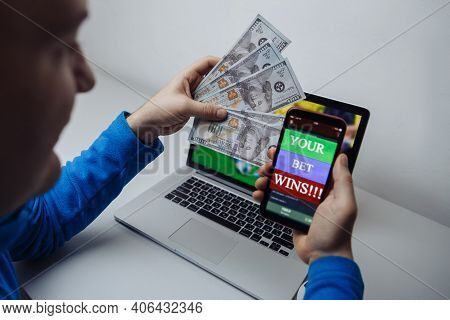 Lucky Male Winner At Football Betting With Dollar Bills And Phone In Hands. Betting And Gambling Con