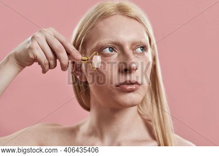 Young Caucasian Man With Long Blond Hair Massaging Under Eye Zone Using Quartz Roller While Standing