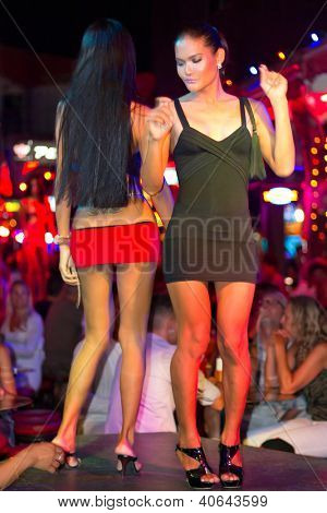 PATONG, THAILAND - NOV 10:  Unidentified individuals dancing on the street of Patong at night. This neighborhood is famous from the nigh life and sex tourism, Patong, Thailand, Nov.10, 2012.