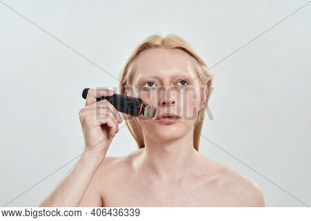 Young Caucasian Man With Long Fair Hair Using Cordless Trimmer On Beard Area While Standing On Light