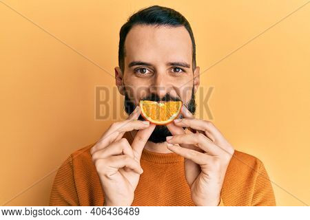 Young man with beard holding orange slice on mouth as funny smile looking positive and happy standing and smiling with a confident smile showing teeth