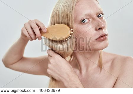 Portrait Of Young Caucasian Man Grooming His Long Fair Hair With Wooden Comb While Standing On White