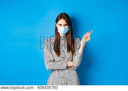 Covid-19, Social Distancing And Healthcare Concept. Angry Young Woman In Medical Mask Frowning, Poin