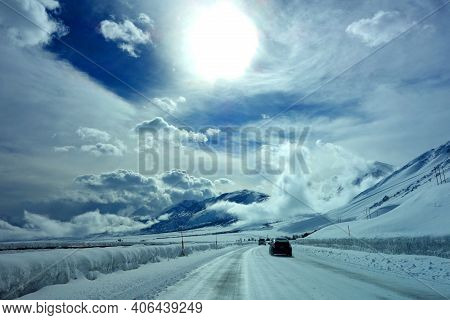Road To Mammoth Lakes Covered In Snow, With Cloud Filled Party Sunny Skies