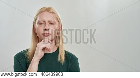 Young Caucasian Man With Long Fair Hair Looking Down To Side While Posing With Hand Under His Chin O