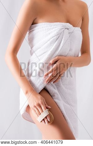 Cropped View Of Young Woman Exfoliating Skin On Leg With Brush On White.
