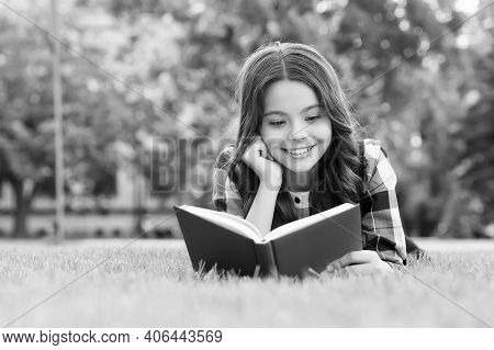 To Succeed You Must Read. Happy Kid Read Book Lying On Green Grass. School Library. Literacy Educati