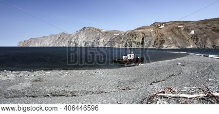 Landscape Of The Northern Sea Coast With  Tugboat And  Boat On The Shingle Shore. The Coastline Of T