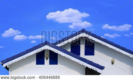Front View Of Blue Fiber Cement Tile Roof In Different Level With Dripping Eave On White Wooden Hous