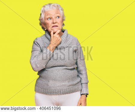 Senior grey-haired woman wearing casual winter sweater thinking worried about a question, concerned and nervous with hand on chin