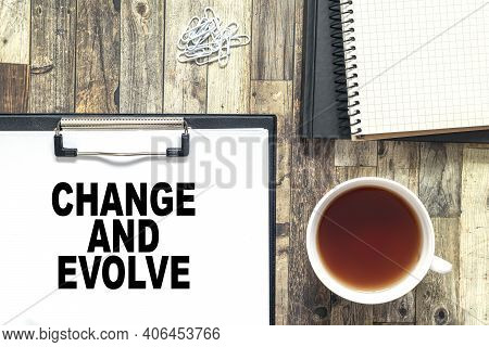 Text Change And Evolve With Cofee Cup, Book,notepad,pen And Pencils On The Wooden Background. Busine