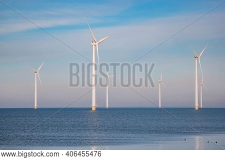 Offshore Windmill Park With Stormy Clouds And A Blue Sky, Windmill Park In The Ocean. Netherlands .