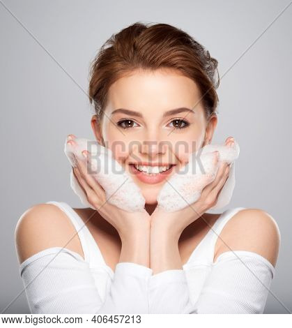 Beautiful face of young caucasian woman with perfect healthy skin, isolated.   Pretty white smiling  model caring of face. Beauty treatment concept. Skin care concept.
