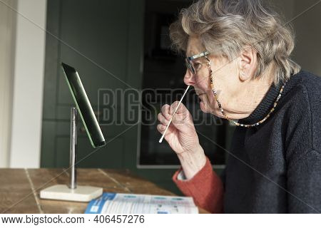 A Woman Looing In A Mirror Taking A Covid-19 Home Testing Nasal Swab