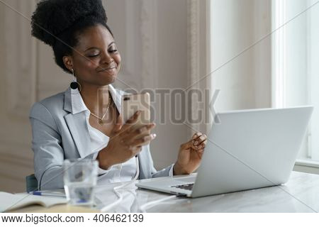 Smiling Afro Woman In Blazer Take A Break Holding Mobile Phone Surfing Internet Working At Laptop Co