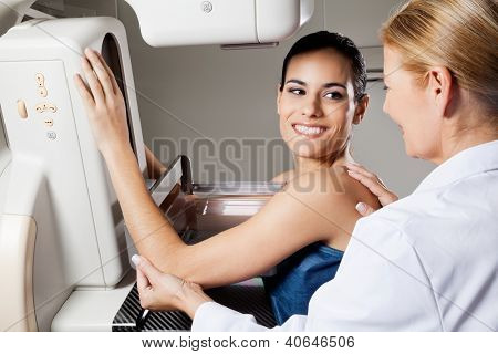 Happy female patient looking at doctor while undergoing mammogram x-ray test