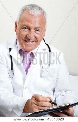 Portrait of senior male doctor smiling while writing on clipboard
