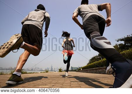 Three Young Asian Adults Running Jogging Outdoors, Rear And Low Angle View