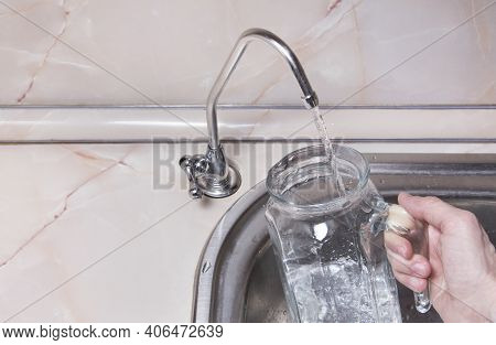Pouring Drinkable Water Into Glass Jug From Water Filter. Closeup Of Sink And Faucet. Filtered Water