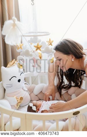 Mom Stands At The Babys Cradle And Holds The Handles Of A Newborn Girl.