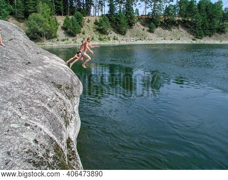 Turochak, Altai Republic, Russia - August 03, 2005: Two Boys Jump Into The Cold Waters Of The Biya R