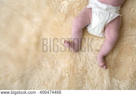 Newborn Baby Legs With White Nappy, Diaper On A Fur Background.