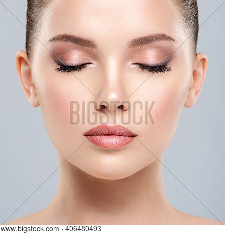 Closeup portrait of a  face of the young pretty girl with a healthy skin. Calm  face of young white woman with a clean skin. Skin care concept.