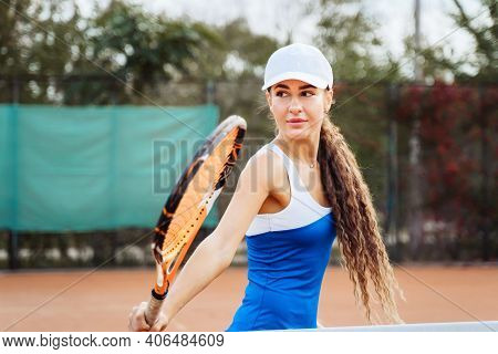 Professional Tennis Player Doing Sport On The Court. She's About To Hit The Ball, Suspended In The A