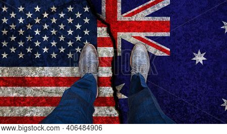 Business Man Stands On Cracked Flags Of Usa And Australia. Political Concept