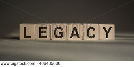 A Wooden Blocks With The Word Legacy Written On It On A Gray Background.