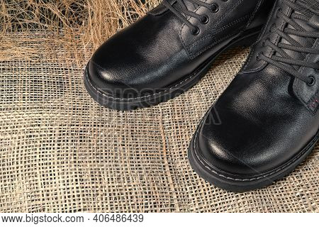 Black Boots Made Of Genuine Leather. Men's Winter Shoes With Laces, Fashionable Style. On A Straw Ba