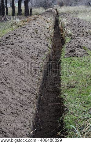 An Empty Long Trench For A Power Cable Is Dug In The Woods. Earthworks, Underground Utilities, Indus