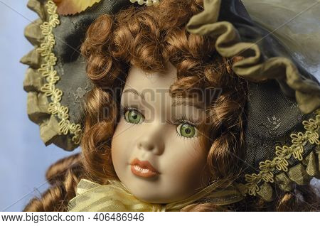 Close-up Of A Vintage Doll's Head. Adorable Realistic Toy With Green Eyes. Doll's Dress With Flowers
