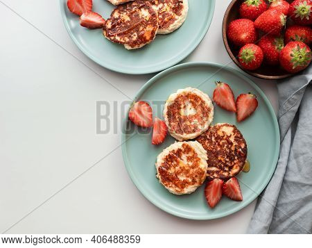 Sweet Cheese Pancakes On Plate Served Strawberries. Cottage Cheese Pancakes, Syrniki, Ricotta Fritte