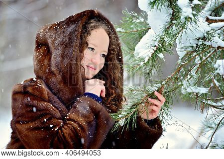 Image Of A Cute Young Girl In A Fur Coat On A Sunny Winter Day In The Park. The Girl Looks Tenderly