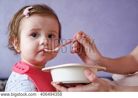 One Year Old Baby Girl Eating Soup. Mother Gives Baby Food From A Spoon.