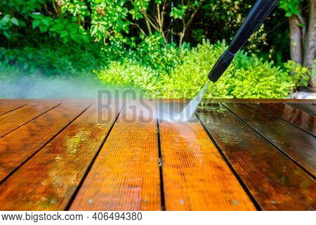 Cleaning The Terrace With A Pressure Washer - High-pressure Cleaner On The Wooden Surface Of The Ter
