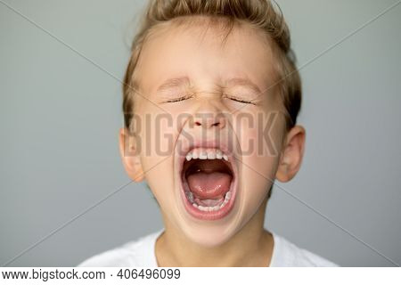 Little Boy Screams With Closed Eyes. Detached Young Man On A Gray Background Opened His Mouth Wide,