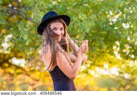 Portrait Of A Beautiful Girl Against A Background Of Blurry Foliage, The Girl Temptingly Covered Her