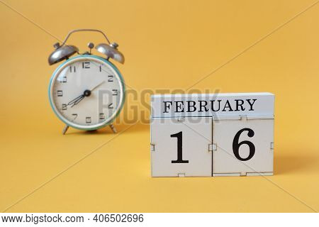 Calendar For February 16: Cubes With The Number 16 And The Name Of The Month, Alarm Clock On A Yello